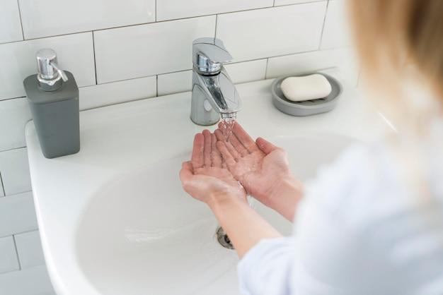 Alto angolo di donna che si lava le mani