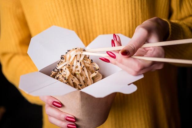 Alto angolo di donna con scatola di noodles