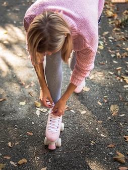 Alto angolo di donna in calze legare i lacci delle scarpe su pattini a rotelle