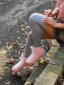 Alto angolo di donna in pattini a rotelle con calze