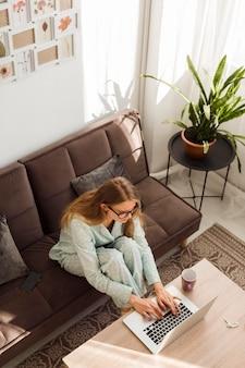 Alto angolo di donna in pigiama che lavora a casa