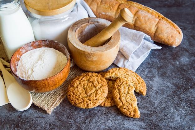 Alto angolo di farina con biscotti e pane