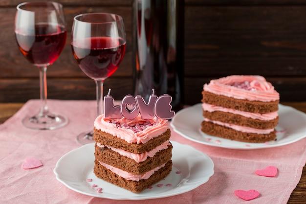 Alto angolo di fette di torta a forma di cuore con bicchieri di vino