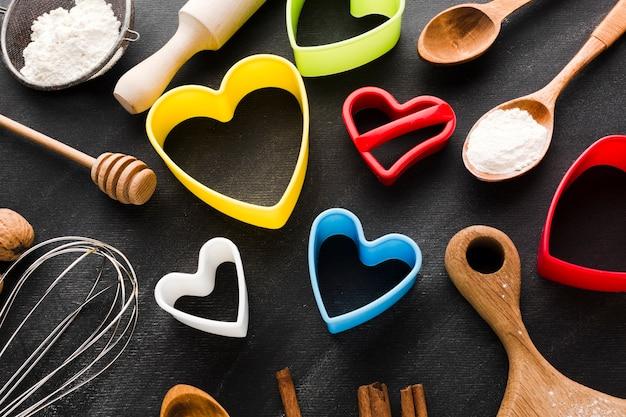 Alto angolo di forme colorate di cuore con utensili da cucina
