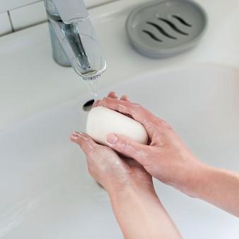 Alto angolo di lavaggio delle mani con saponetta e acqua