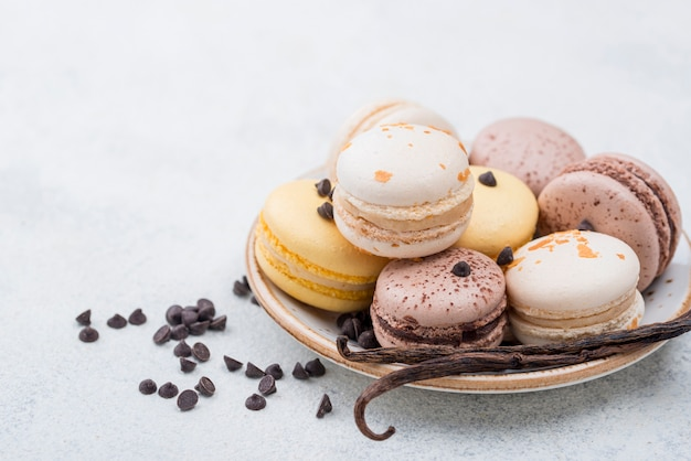 Alto angolo di macarons con gocce di cioccolato e baccello di vaniglia