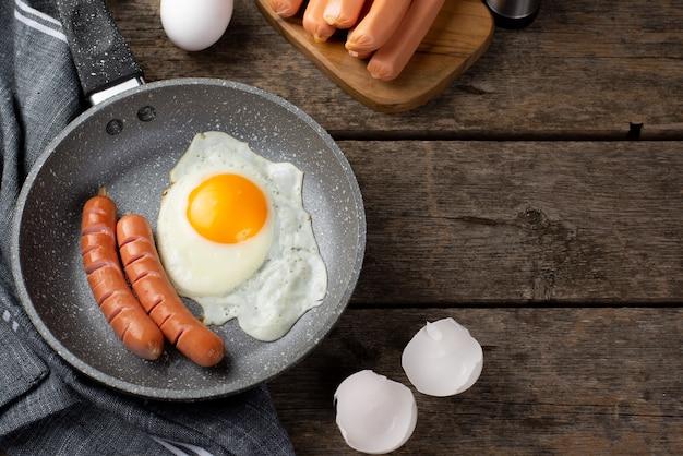 Alto angolo di padella con uovo e salsicce per la colazione