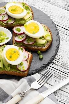 Alto angolo di panini con uova e avocado su ardesia con posate