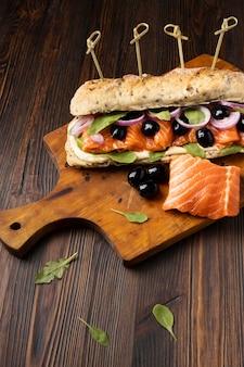 Alto angolo di panino con salmone e olive