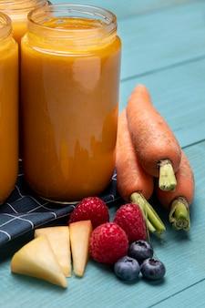Alto angolo di pappe in vasetti con frutta e carote