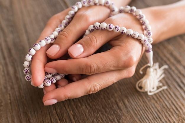 Alto angolo di persona che prega con il rosario in mano