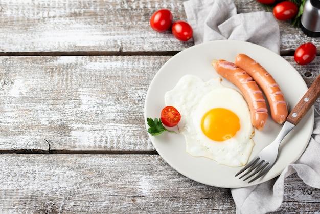 Alto angolo di piastra con salsicce e uova per la colazione