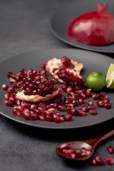 Alto angolo di piastra con semi di melograno e cucchiaio