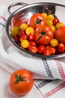 Alto angolo di pomodori in una ciotola con un panno
