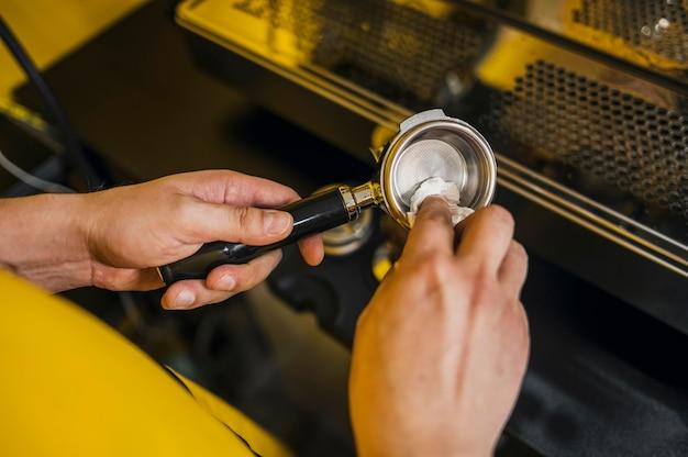 Alto angolo di pulizia della tazza da barista per macchina da caffè
