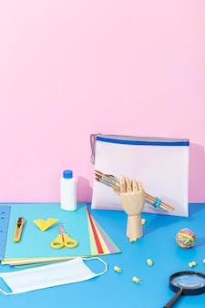Alto angolo di ritorno a materiale scolastico con forbici e lente d'ingrandimento