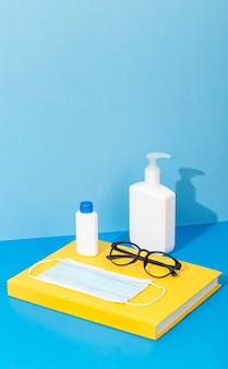Alto angolo di ritorno a materiale scolastico con libro e disinfettante per le mani