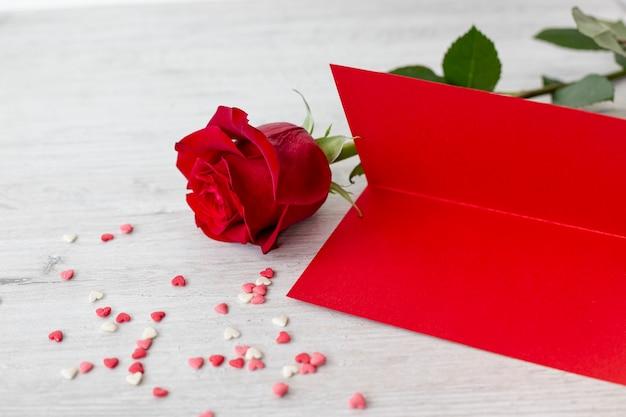 Alto angolo di rosa con carta e cuori per san valentino