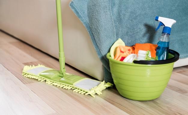 Alto angolo di scopa e secchio con prodotti per la pulizia