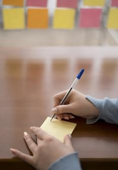 Alto angolo di scrittura della donna sulle note appiccicose mentre all'ufficio