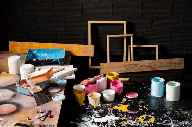 Alto angolo di studio di pittura con lattine e cornici