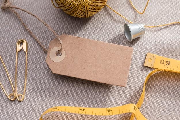Alto angolo di tag con metro a nastro e ditale