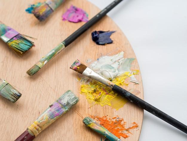 Alto angolo di tavolozza di colori con pennelli