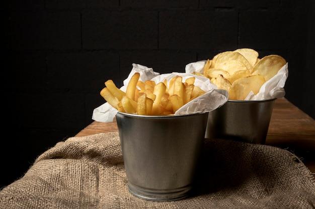 Alto angolo di tazze di metallo con patatine fritte e patatine