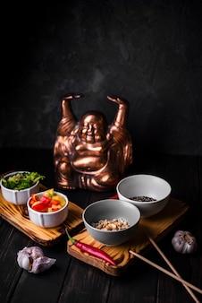Alto angolo di tazze di verdure con statua
