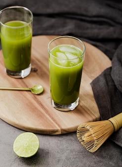 Alto angolo di tè matcha in bicchieri con cubetti di ghiaccio e lime