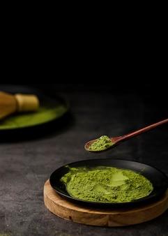 Alto angolo di tè matcha in polvere sul piatto