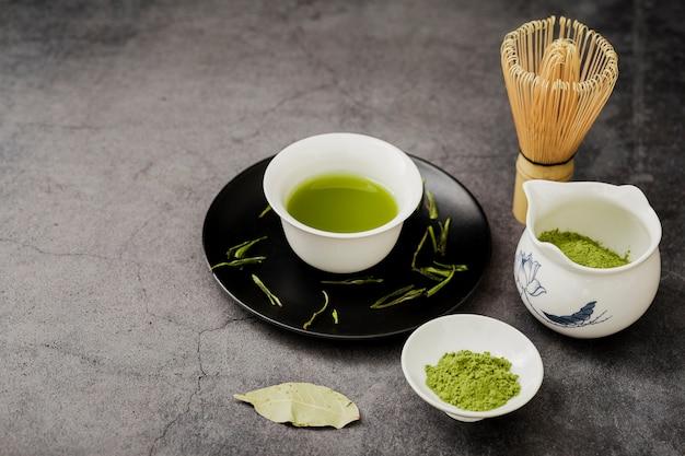 Alto angolo di tè matcha in tazza con piatto e foglia