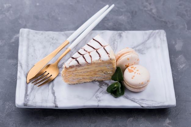 Alto angolo di torta sul piatto con posate e macarons