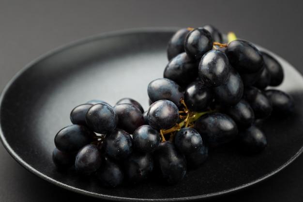 Alto angolo di uva nera sul piatto