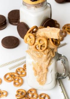 Alto angolo di vasetti di dessert con biscotti e salatini