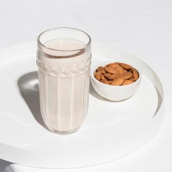 Alto angolo di vetro con latte e mandorle