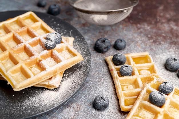 Alto angolo di waffle con mirtilli e ricoperto di zucchero a velo