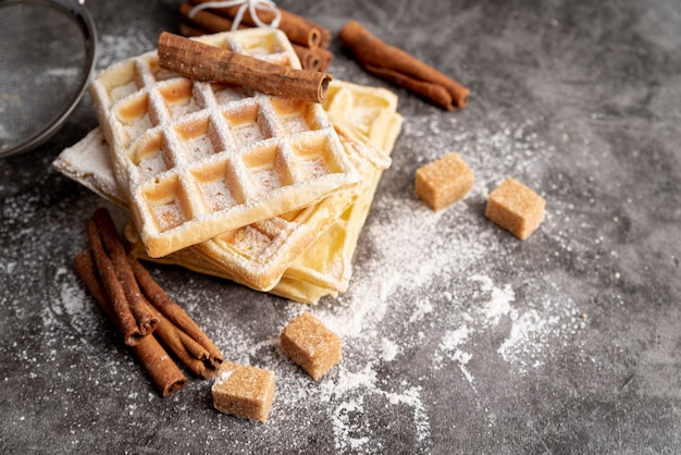 Alto angolo di waffle impilati con bastoncini di cannella e zollette di zucchero