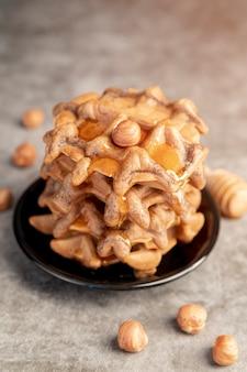 Alto angolo di waffle impilati sul piatto con miele e nocciole