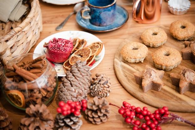 Alto angolo di winterberry con pigne e biscotti