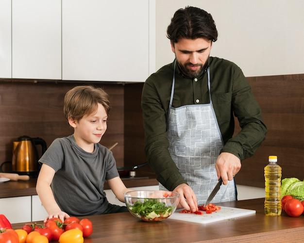 Alto angolo figlio e padre che cucinano insalata