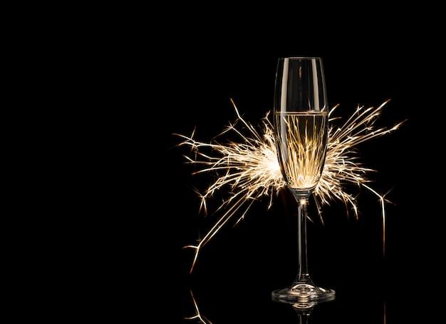 Alto bicchiere di champagne nel bagliore delle luci del bengala