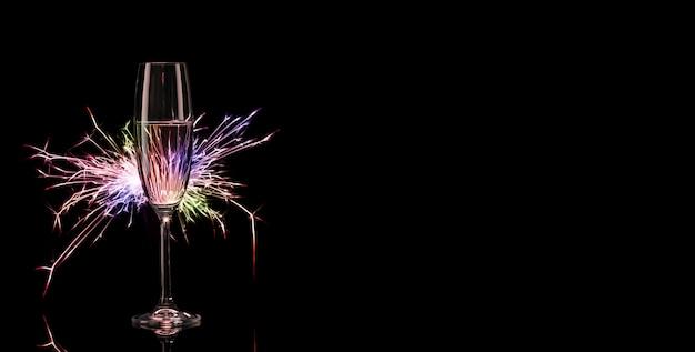 Alto bicchiere di champagne nello splendore delle luci colorate del bengala