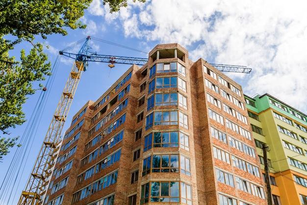 Alto edificio moderno in costruzione con gru a torre e albero verde