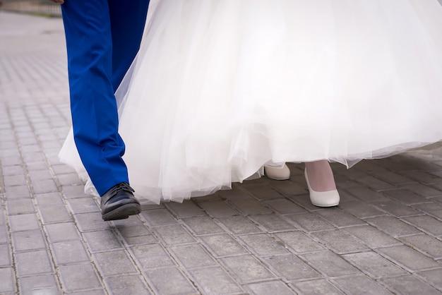 Alto vicino delle gambe della sposa e dello sposo