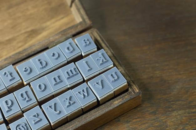 Alto vicino di alfabeto di legno del bollo per fondo.