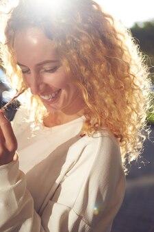 Alto vicino sorridente della donna dell'acconciatura riccia del giovane redgead al sole