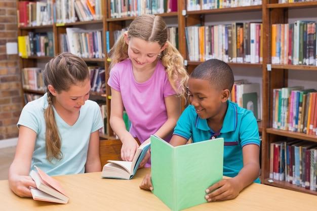 Alunni carini che leggono nella biblioteca