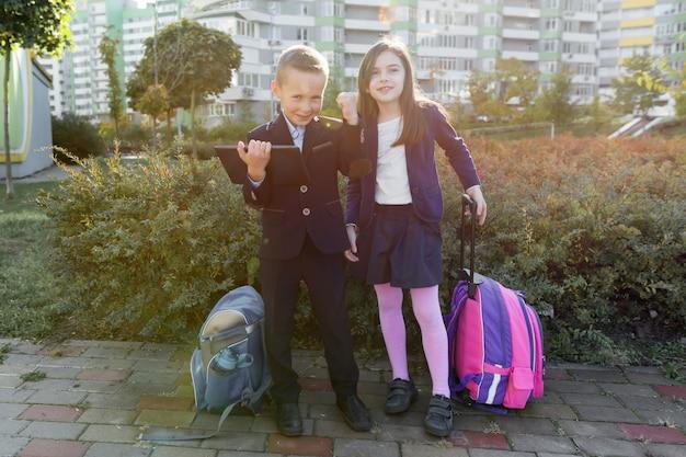 Alunni della ragazza e del ragazzo a scuola primaria con la compressa digitale