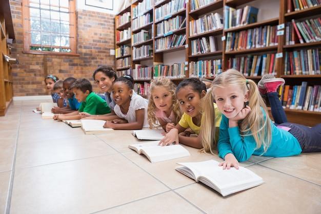 Alunni ed insegnante svegli che si trovano sul pavimento in biblioteca